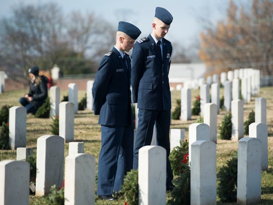 Civil Air Patrol cadets Andrew Clapp, left, and Connor Falin pause to show respect at individual headstones during Wreaths Across America at Knoxville National Cemetery on Saturday, December 16, 2017.