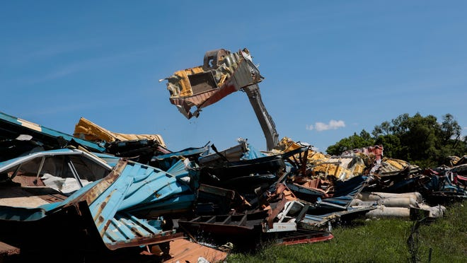 "An excavator lifts pieces of the ""Cargominium"" apartment complex, 1562 Old Leonard Ave., during demolition on Thursday."