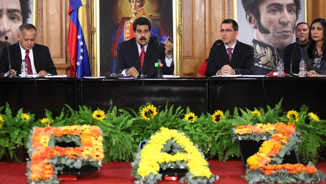Venezuelan President Nicolas Maduro, center, speaks during a meeting at the Miraflores presidential palace in Caracas on February 26, 2014.