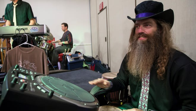 Costumes mixed with beer and wine tasting were part of the 3rd annual charity Casks & Casket Homebrew that took place at the Oshkosh Convention Center November 1, 2014. Robin Cardell plays hand drums with the band Sly Joe & the Smooth Operators.