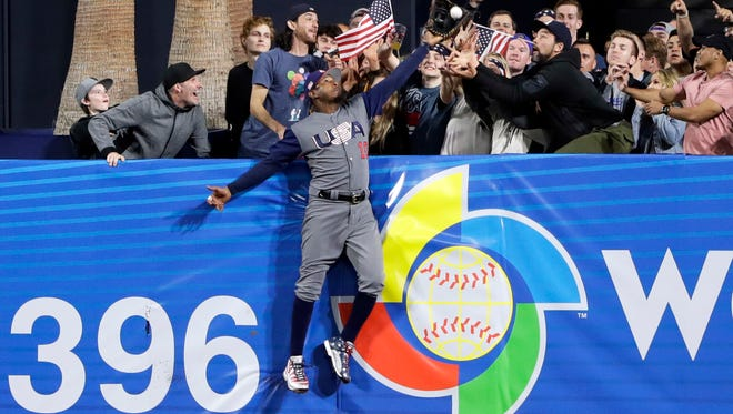 Adam Jones reaches beyond the center field fence at Petco Park to rob Manny Machado - his Baltimore Orioles teammate - of a home run in the World Baseball Classic.