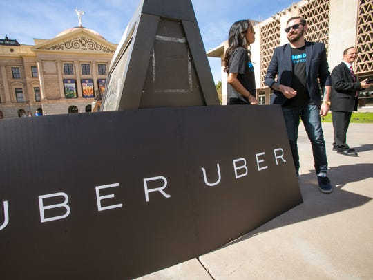 Uber Arizona employees stand outside the state Capitol as they wait to attend a hearing for a bill that would allow ride-sharing in Phoenix on Feb. 18, 2014.