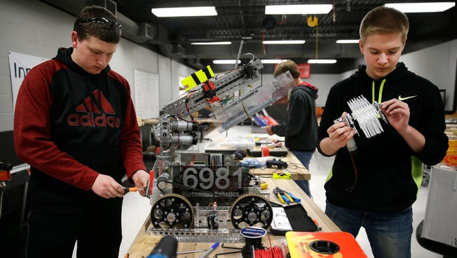 Colton Nelson, a junior at Hortonville High School, and Dakota Snyder, a freshman, make adjustments to the robot they will use at the FIRST Tech Challenge World Championships next week in St. Louis.
