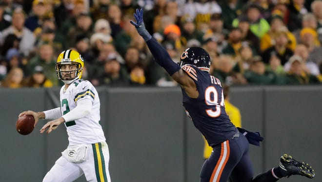 Green Bay Packers quarterback Aaron Rodgers (12) throws against Chicago Bears outside linebacker Leonard Floyd (94) in the first half at Lambeau Field.