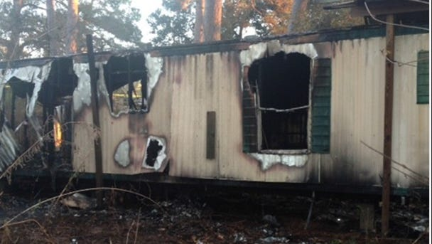 A badly burned body was found Monday in this abandoned mobile home by Natchitoches firefighter following a fire there.