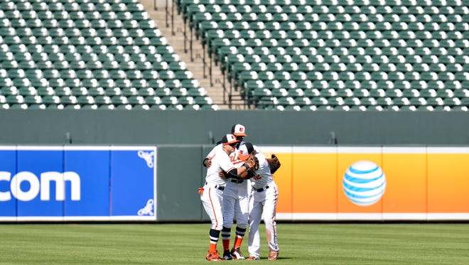 Orioles outfielder embrace after defeating Chicago White Sox 8-2 on a day no fans were allowed at Camden Yards.