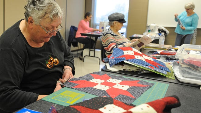 Pat Minks works on quilts for Quilts of Valor at Morningside Community Center in Sioux Falls, S.D., Friday, Oct. 23, 2015. Quilts of Valor are given to veterans. The Sioux Falls Quilt GuildÕs quilt show Oct. 31 and Nov. 1.