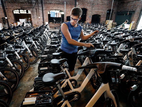 Taylor Desjardius helps assemble 600 for-rent bicycles