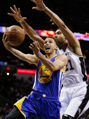 Apr 5, 2015; San Antonio, TX, USA; Golden State Warriors point guard Stephen Curry (30) shoots the ball under pressure from San Antonio Spurs power forward Tim Duncan (21) during the second half at AT&T Center. Mandatory Credit: Soobum Im-USA TODAY Sports