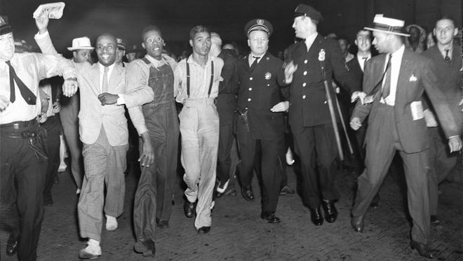 """In this July 26, 1937 file photo, police escort two of the five recently freed """"Scottsboro Boys,"""" Olen Montgomery, wearing glasses, third left, and Eugene Williams, wearing suspenders, fourth left, through the crowd greeting them upon their arrival at Penn Station in New York. In a final chapter to one of the most important civil rights episodes in American history, Alabama lawmakers voted Thursday, April 4, 2013, to give posthumous pardons to the nine black teens who were wrongly convicted of raping two white women in 1931."""