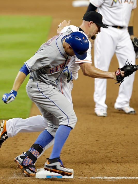 New York Mets' Michael Cuddyer, foreground, is safe at first base as he beats Miami Marlins relief pitcher Mike Dunn in the eighth first inning of a baseball game, Wednesday, April 29, 2015, in Miami. The Marlins won 7-3. (AP Photo/Alan Diaz)