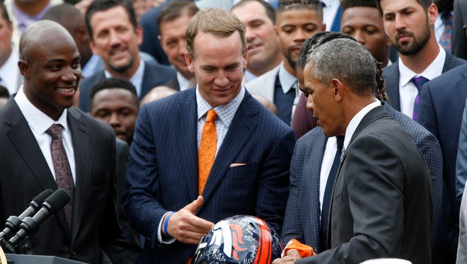 Jun 6, 2016; Washington, DC, USA; Denver Broncos outside linebacker DeMarcus Ware (L) looks on as retired Denver Broncos quarterback Peyton Manning (2L) presents President Barack Obama (M) a team autographed Broncos helmet at a ceremony honoring the NFL Super Bowl Champion Broncos in the Rose Garden at The White House.
