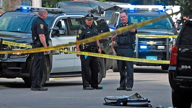 Officers work the scene where a Weymouth police officer was shot and killed after a foot chase with a suspect following a vehicle crash on July 15, 2018, in Weymouth, Mass.