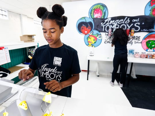 Mallory Iyana, 12, inputs inventory before the grand opening of her new store Angels and Tomboys that she will run along her sister and mother on Summer Avenue.