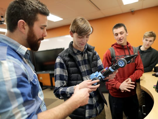 Media speciaiist Kevin Hietpas, left, discusses a remote control car project with students Austyn Bella, center left, Trevor Verhagen and Ben Brochtrup, right, at Kaukauna High School. Wm. Glasheen/USA TODAY NETWORK-Wisconsin