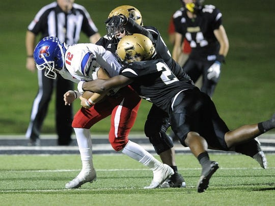 Thomas Metthe/Reporter-News Abilene High defensive lineman Noah Perez (99) and linebacker Terrell Franklin (20) sack Cooper quarterback Austin Smith (12) during the fourth quarter of the Eagles' 55-38 win in the crosstown football game on Friday, Sept. 9, 2016, at Shotwell Stadium.