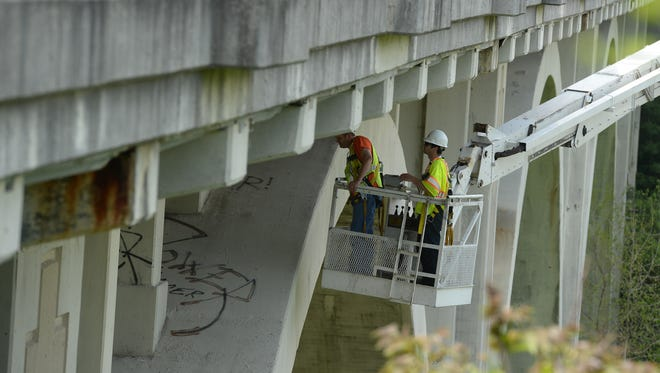 Inspectors look at the underside of the South G Street bridge on May 13, 2014.