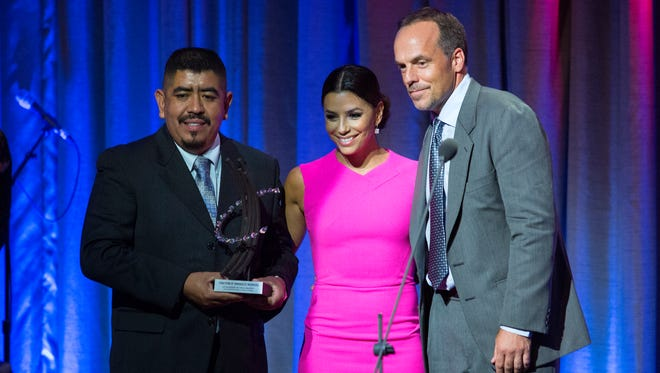Greg Asbed,Co-founder,Coalition of Immokalee Workers, right, stands with Lucas Benitez,Co-founder,Coalition of Immokalee Workers as they stand with actress and activist Eva Longoria after accepting an award at theClinton Global Citizen Awards dinner in New York Sunday, Sept. 21, 2014. (AP Photo/Craig Ruttle)