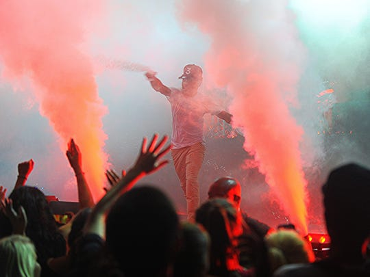 Chance the Rapper flings water on the crowd at the Fox Theatre on Sunday.