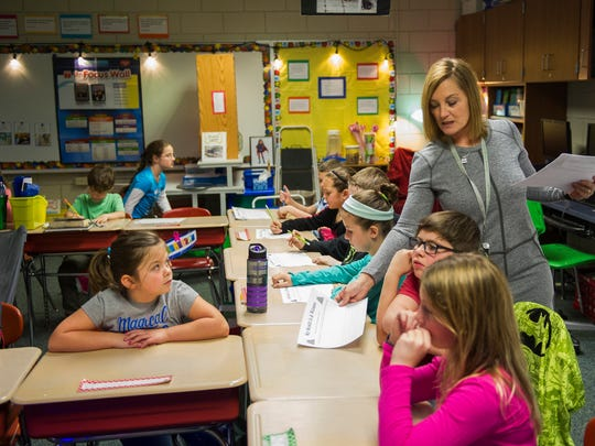 Lisa Porter, of Newburgh, passes out papers to her third grade classroom at Sharon Elementary in Newburgh.