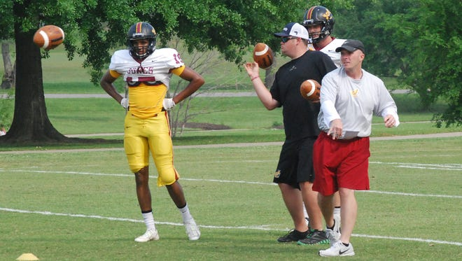 JCJC offensive coordinator and wide receivers coach John Carr throws a pass during drills with Bobcat wideouts on Monday.