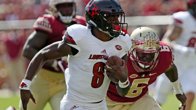 Louisville's Lamar Jackson gets past Florida State's Matthew Thomas to score in the first quarter of an NCAA college football game, Saturday, Oct. 21, 2017, in Tallahassee Fla. (AP Photo/Steve Cannon)