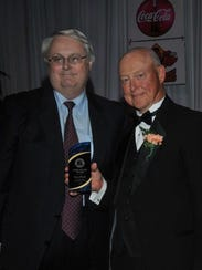 Gary Smith, right, receives the Eddie Meath Award from
