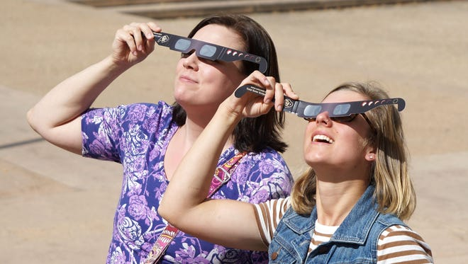 Carrie Trochim, 34, on left, and colleague, Kirsten Polley, 26 test out eclipse glasses on the University of Colorado's Boulder campus on Aug. 15, 2017. They were among the last customers to snap up glasses from the bookstore before it ran out of its stock of 10,000 pairs.