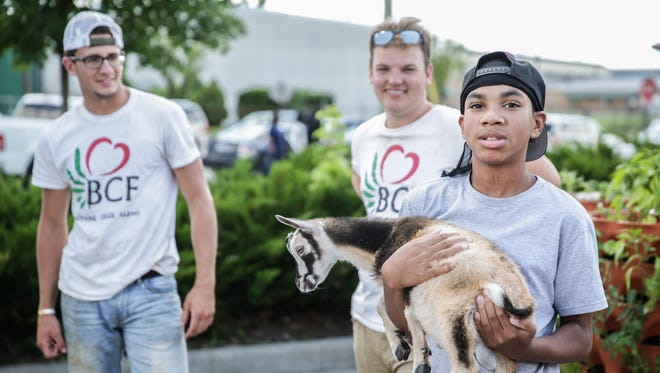 Trey Pace, right, holds Wookie a Nigerian Dwarf Goat from The Rolling Harvest truck and Brandywine Creek Farms which made it's debut during the Circle Up Indy event at IPS School 51 in Indianapolis on Saturday, June 24, 2017. The Rolling Harvest truck will make weekly stops at east side locations that are being hard-hit by Marsh closings.