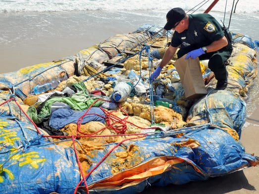 Brevard County Sheriff's Deputy Chris Hendrix looks through a makeshift raft containing items including clothing, water bottles, syringes and other medical supplies that washed up on a Brevard beach on Monday, April 14, 2014.