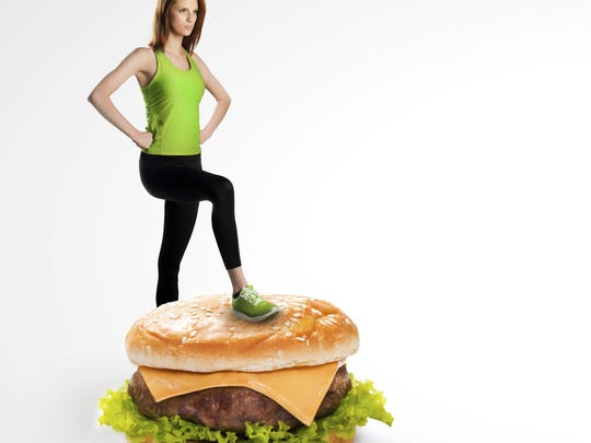 Fit woman standing on a cheeseburger