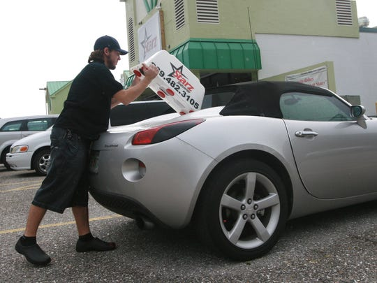 Stefan Santiago, a delivery driver for Starz Pizzeria, puts a magnetic sign on his vehicle before making deliveries  Thursday evening.