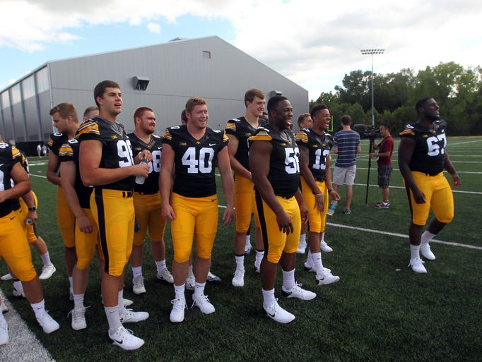Iowa players joke around as a teammate poses for photos