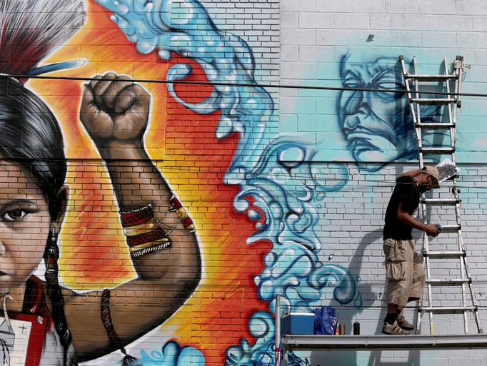 Detroit artist Syntex, gets ready to go on a ladder