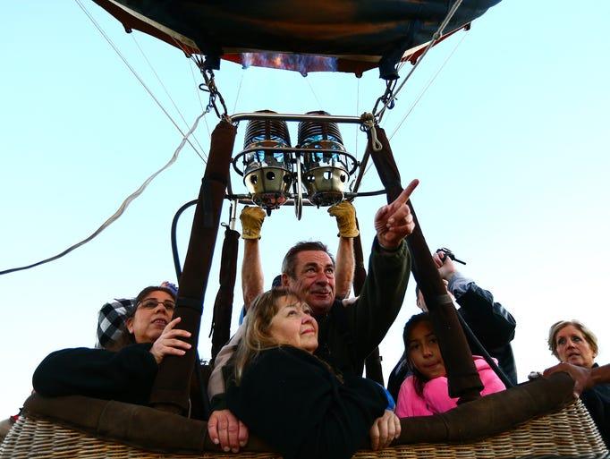 A hot air balloon rider points as the balloon takes