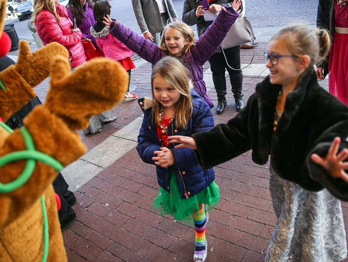Children's faces light up as holiday characters greet