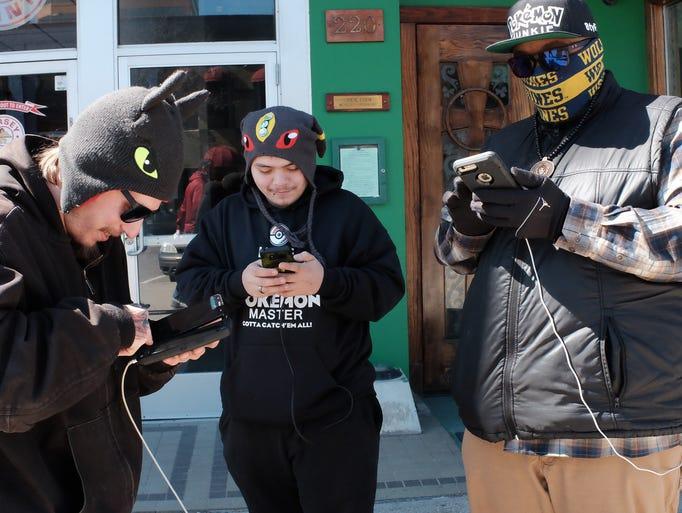 Three guys play Pokemon Go during the scheduled Pokemon