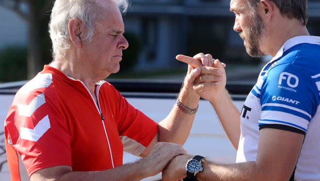 Harald Vik, who is blind and deaf communicates with his interpreter, Robert Skarsbakk Friday morning before heading out on bicycles as part of a multi-day ride from Brookings to Lincoln, Neb, Aug 22, 2014. Vik and interpreter, Torben Loekaas were stuck by a car while northbound on Marion Road near Madison Street later Friday morning.