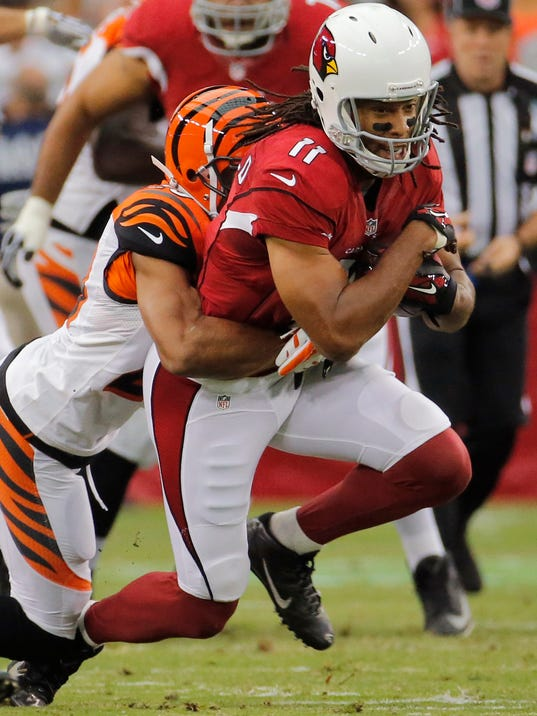 Arizona Cardinals wide receiver Larry Fitzgerald (11) pulls in a pass as Cincinnati Bengals cornerback Leon Hall makes the tackle during the first half of an NFL preseason football game, Sunday, Aug. 24, 2014, in Glendale, Ariz. (AP Photo/Matt York)