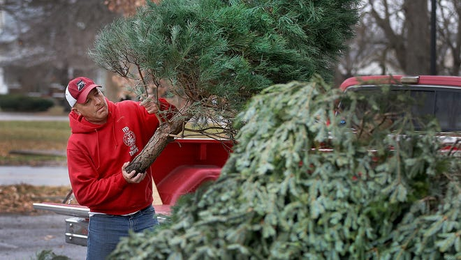 Kevin Kieffer drops off his family's Christmas tree at the disposal site at Garfield Park on Monday. Other free tree disposal sites in Marion County are: Broad Ripple Park, Ellenberger Park, Gustafson Park, Krannert Park, Northwestway Park, Perry Park, Riverside Park and Sahm Park.