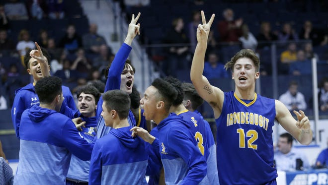 Irondequoit's Tanner Pioch celebrates with the team a 58-51 win over Athena at the Blue Cross Arena at the Community War Memorial.