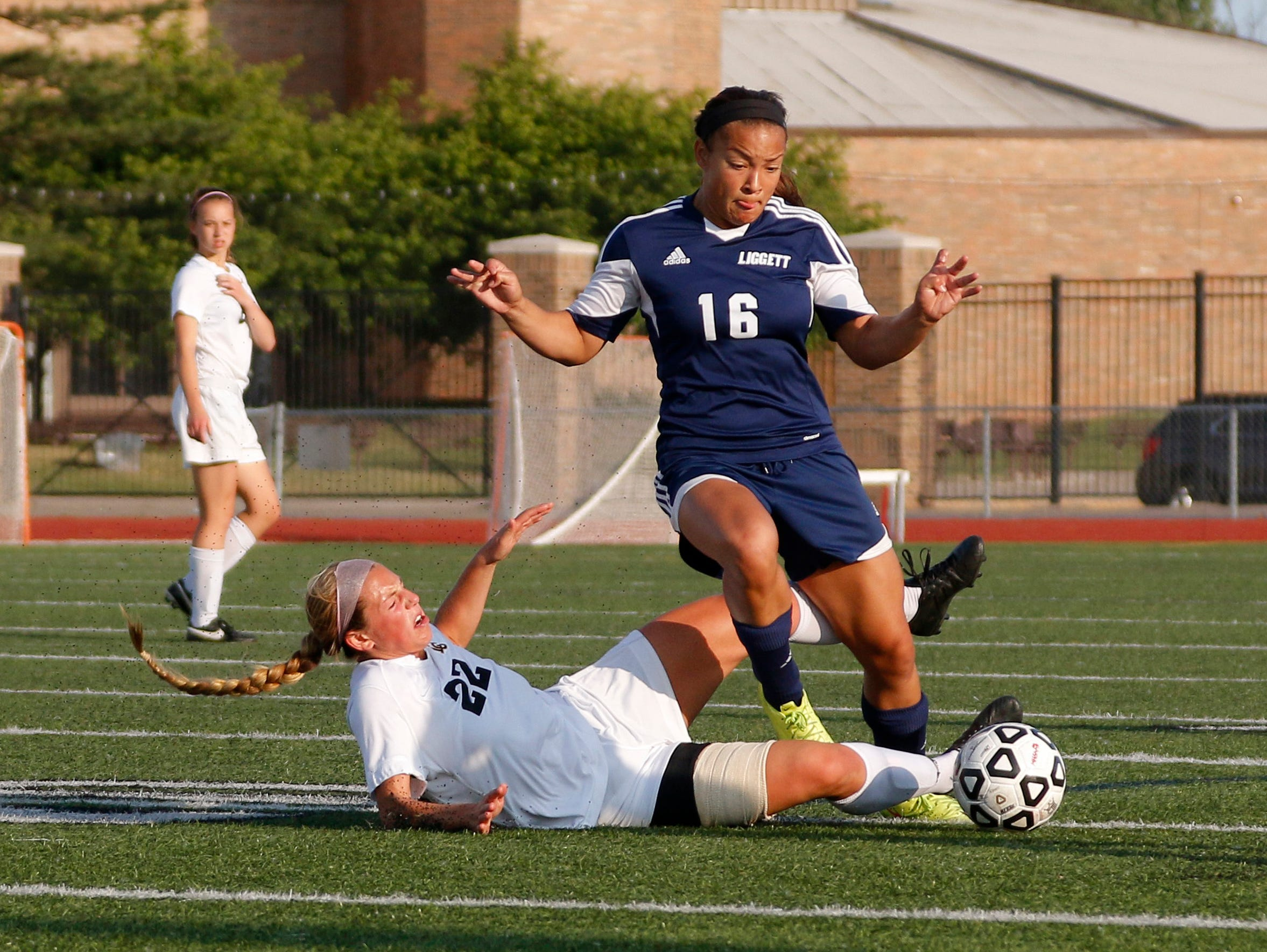 Lansing Christian's Abby Krueger, left, and University Liggett's Alexis Wenger battle for the ball during their MHSAA quarterfinal game Tuesday, June 14, 2016, at Troy Athens High School.
