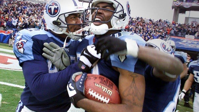 """Yancy Thigpen, left, congratulates Titans wide receiver Kevin Dyson after Dyson scored on """"Home Run Throwback"""" with seconds to play in a 2000 playoff game against Buffalo at Adelphia Coliseum."""