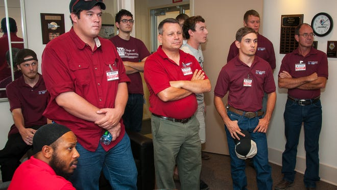 NMSU engineering students and faculty listen to Las Cruces mayor Ken Miyagishima read a proclamation in honor of National Manufacturing Day at the offices of Calculex in October 2015.