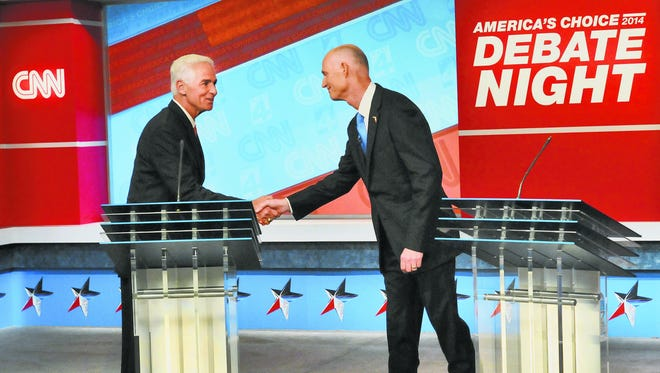 Democratic candidate Charlie Crist, left, and Republican Gov. Rick Scott shake hands before their live television debate in 2014.