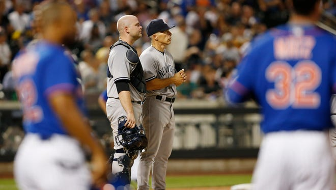 New York Yankees catcher Brian McCann (34) and New York Yankees manager Joe Girardi wait out a pitching change after Girardi removed Yankees starting pitcher CC Sabathia in the sixth inning of an interleague baseball game against the New York Mets, Monday, Aug. 1, 2016, in New York.