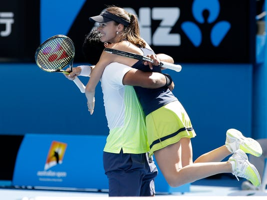 Martina Hingis of Switzerland celebrates with her partner Leander Paes of India after defeating Hsieh Su-Wei of Taiwan and Pablo Cuevas of Uruguay in their mixed doubles semifinal match at the Australian Open tennis championship in Melbourne, Australia, Friday, Jan. 30, 2015. (AP Photo/Lee Jin-man)