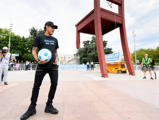 """France's Paris Saint Germain, PSG, soccer team Brazilian striker Neymar Jr poses with a ball in front of the """"Broken Chair"""" sculpture, a symbol for victims of the anti-person mines created in 1997 for Handicap International, during his presentation as new goodwill ambassador of Handicap International, in front of the European headquarters of the United Nations, UN, in Geneva, Switzerland, Tuesday, Aug. 15, 2017. The Brazilian football player is the new goodwill ambassador of Handicap International which supports people with disabilities and other vulnerable populations living in conflict and disaster zones and in situations of exclusion and extreme poverty. (Laurent Gillieron/Keystone via AP)"""