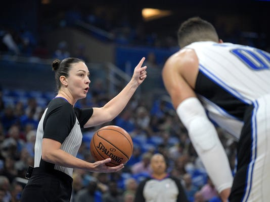 FILE - In this Oct. 18, 2017, file photo, official Lauren Holtkamp gestures in front of Orlando Magic forward Aaron Gordon during the first half of an NBA basketball game against the Miami Heat, in Orlando, Fla. The G League season opens Friday night, Nov. 3, 2017, and there will be someone on the court in places like Grand Rapids or Greensboro or Des Moines whose next job will be in the NBA. That isn't limited to players. Or to men. Nearly one-third of the referees in the G League this season are women, and some _ like dozens of players, coaches, front-office staff and refs _ are moving closer to realizing NBA hopes. (AP Photo/Phelan M. Ebenhack, File)