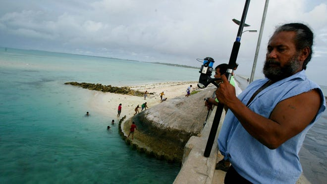 In this March 30, 2004, file photo, a man fishes on a bridge on Tarawa atoll, Kiribati. The island nation of Kiribati established a large shark sanctuary that will help ensure the creatures are protected across much of the central Pacific. Vice President Kourabi Nenem said at the sanctuary's launch on Friday, Nov. 18, 2016, that the nation was committed to protecting sharks from exploitation and overfishing. (AP Photo/Richard Voge, File)